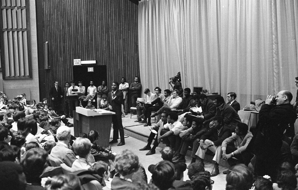 PHOTO PAUL-HENRI TALBOT, LA PRESSE -- LES ÉTUDIANTS NOIRS DONNENT LEUR VERSION Devant plus d'un millier d'étudiants de l'université sir George Williams, leur confrère de race noire ont donné leur version du cas du professeur Perry Anderson, du département de biologie, qui aurait tenu des propos et adopté des attitudes discriminatoires à leur égard. -30- -aplp- 23 janvier 1969 Négatif monochrome 35 mm.